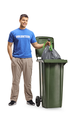 Full length portrait of a young man volunteer throwing waste in a bin isolated on white background
