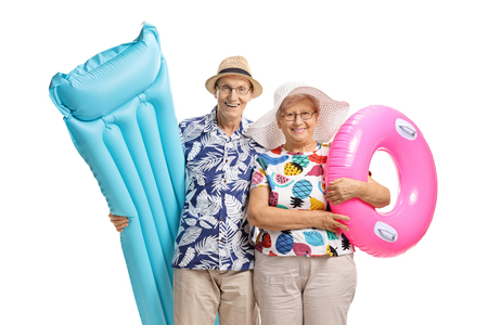 Senior couple with an air mattress and a swimming tire isolated on white background