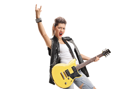 Punk girl with an electric guitar making a horn sign isolated on white background