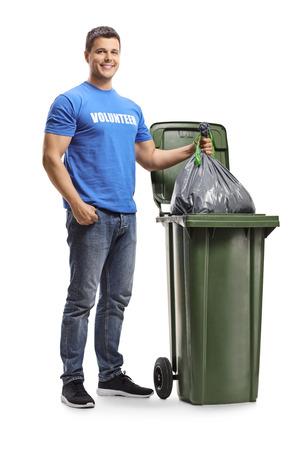 Volledig lengteportret van een jonge mannelijke vrijwilliger die een plastic zak in een bak gooit die op witte achtergrond wordt geïsoleerd Stockfoto