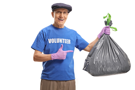 Elderly male volunteer  holding a waste bag and pointing isolated on white background