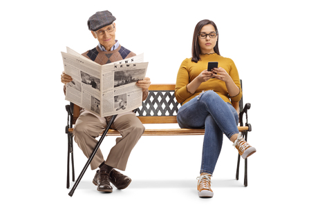 Full length portrait of a young female with a mobile phone and a senior man reading a newspaper on a bench isolated on white background Foto de archivo