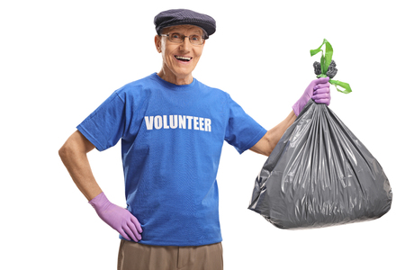 Senior male volunteer smiling and holding a plastic waste bag isolated on white background