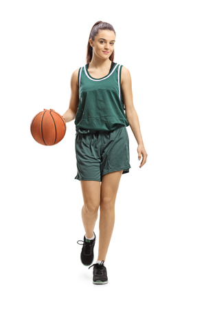 Full length portrait of a female basketball player leading a ball and posing isolated on white background