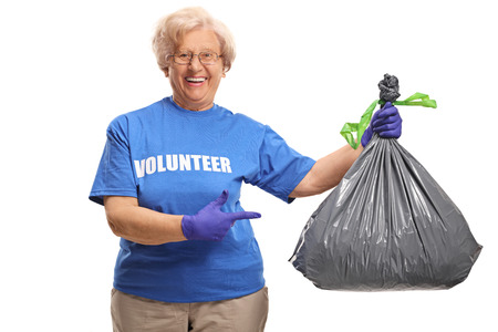 Cheerful senior female volunteer pointing at a waste bag isolated on white background