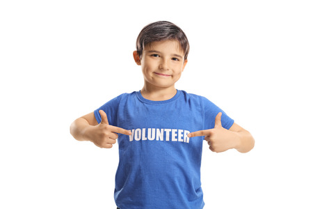 Child volunteer pointing to his blue t-shirt isolated on white background