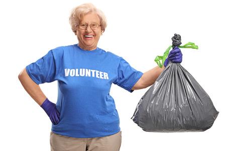 Elderly female volunteer holding a waste bag isolated on white background