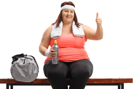 Plus size woman seated on a wooden bench next to a sports bag making a thumb up sign isolated on white background