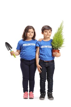 Portrait en pied d'un petit garçon et d'une fille bénévoles tenant une plante et une pelle isolés sur fond blanc Banque d'images