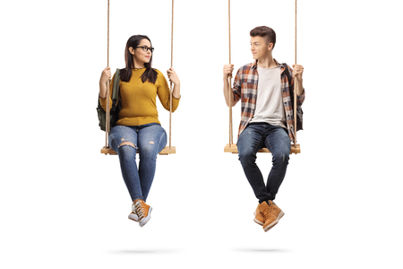 Full length shot of a female and male student on a swing looking at each other isolated on white background