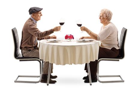 Anciano y mujer haciendo vítores con vino tinto en una mesa aislada sobre fondo blanco.