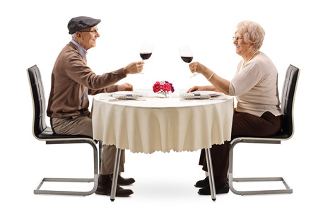 Elderly man and woman making cheers with red wine at a table isolated on white background
