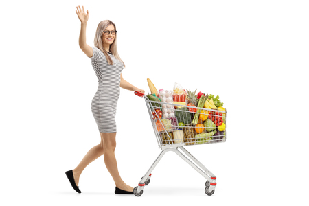 Full length shot of a young woman with a shopping cart full of food products waving isolated on white background Stock fotó