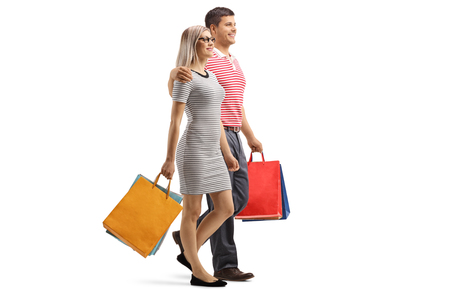 Full length shot of a young couple walking with shopping bags isolated on white background