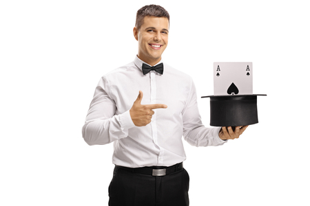 Young smiling magician pointing to a hat with an ace card inside isolated on white background