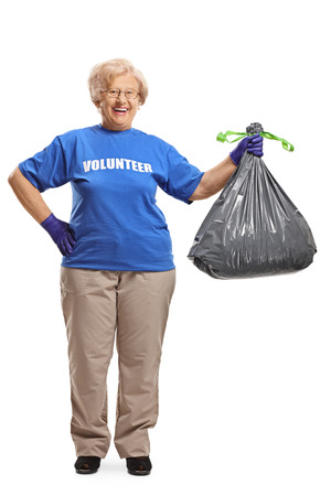 Full length portrait of a senior woman volunteer with a waste bag smiling at the camera isolated on white background