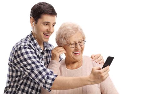 Hombre joven y una mujer mayor escuchando música en un teléfono inteligente aislado sobre fondo blanco.