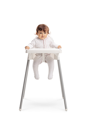 Full length portrait of a baby girl sitting in a feeding chair isolated on white background