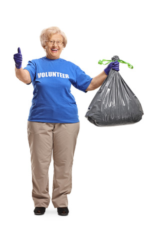 Full length portrait of an elderly woman volunteer with a waste bag giving thumbs up isolated on white background