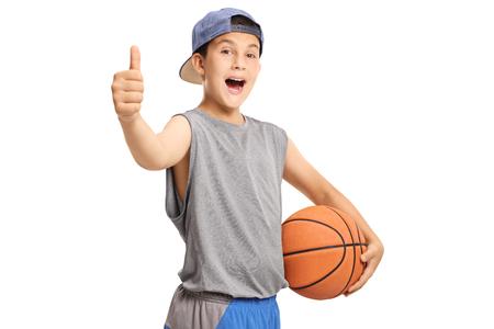 Cool adolescente con una pelota de baloncesto mostrando Thumbs up aislado sobre fondo blanco.