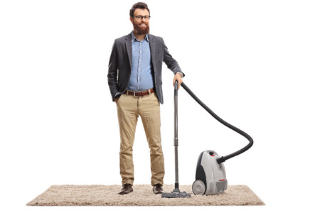 Full length portrait of a young bearded man posing with a vacuum cleaner on a carpet isolated on white background