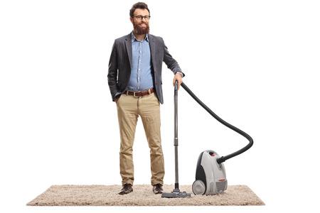 Retrato de cuerpo entero de un joven barbudo posando con una aspiradora sobre una alfombra aislada sobre fondo blanco.