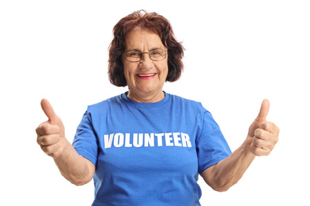 Cheerful elderly female volunteer showing thumbs up isolated on white background