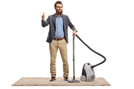 Full length portrait of a young man with a vacuum cleaner on a carpet showing thumbs up isolated on white background Imagens