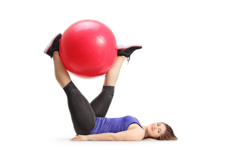 Full length shot of a young female lying exercising with a fitness ball on the floor isolated on white background Stock fotó