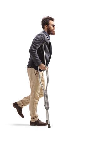 Full length profile shot of a young bearded man walking with crutches isolated on white background Stock Photo
