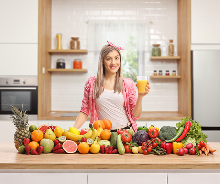 Young woman in a kitchen with a glass of orange juice and a pile of fruits and vegetables
