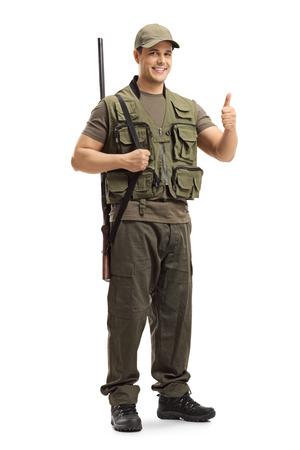 Portrait d'un chasseur avec un fusil de chasse sur son épaule montrant le pouce levé signe isolé sur fond blanc