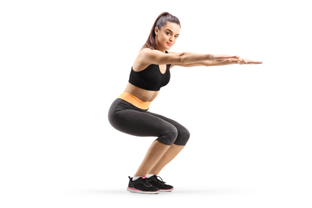 Young woman exercising squats isolated on white background Stock Photo