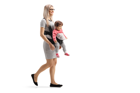 Full length shot of a mother walking with a baby in a carrier isolated on white