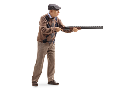 Full length profile shot of an elderly man aiming with a shotgun isolated on white