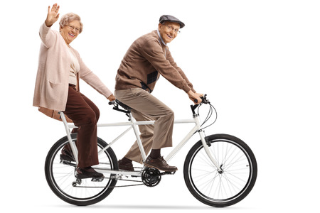 Full length shot of a senior woman and man riding a tandem bicycle and waving isolated on white