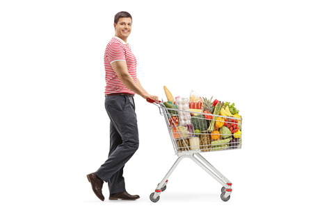 Full length shot of a young man with a shopping cart smiling at the camera isolated on white