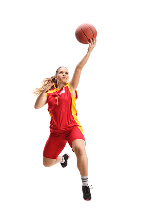 Full length portrait of a female basketball player jumping with a ball isolated on white