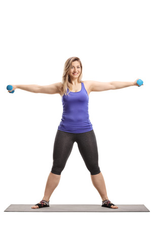 Full length portrait of a young woman stretching arms with dumbbells isolated on white 写真素材