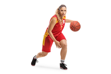 Full length portrait of a female basketball player leading a ball isolated on white