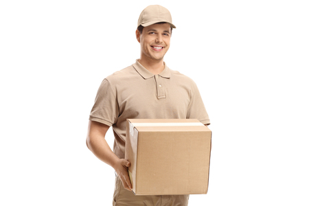 Smiling delivery guy holding a package isolated on white