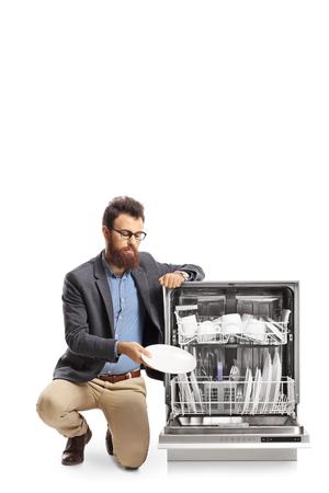 Bearded man loading a dishwasher isolated on white background