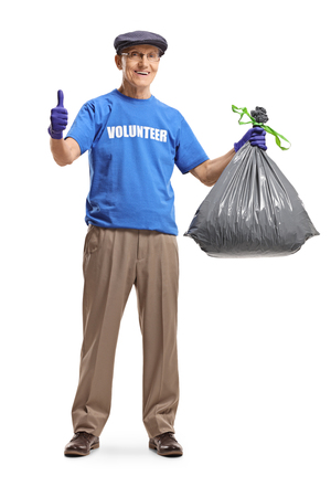 Full length portrait of an elderly man volunteer holding a waste bag and showing thumbs up isolated on white background