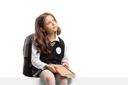 Little schoolgirl holding a book and thinking isolated on white background