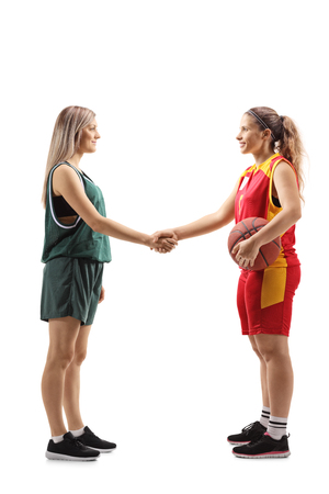 Full length profile shot of two female basketball players shaking hands isolated on white background Banco de Imagens