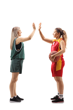 Full length profile shot of two female basketball players gesturing high-five isolated on white background