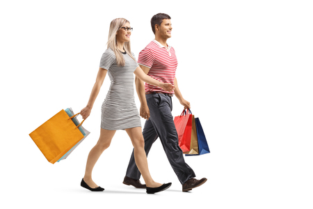 Full length shot of a young man and woman walking with shopping bags isolated on white background