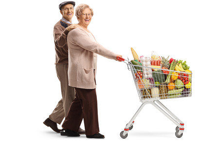 Full length shot of an elderly couple walking and pushing a shopping cart with food products isolated on white background