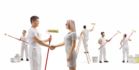 Full length profile shot of a male painter shaking hands with a young woman and workers painting wall isolated on white background