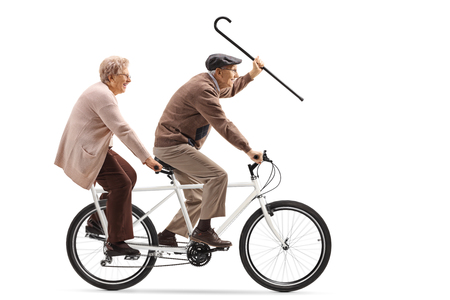 Full length shot of a senior man and woman riding a tandem bicycle and waving with a walking cane isolated on white background Foto de archivo